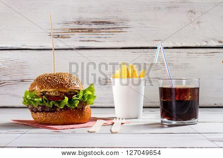 Burger on stick and fries. Cola and fries with burger. White table with beefburger menu. More than enough calories.