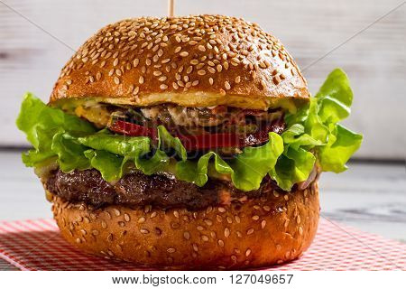 Big burger with sesame buns. Burger laying on bright napkin. Beefburger on white wooden background. Best dish in local cafe.