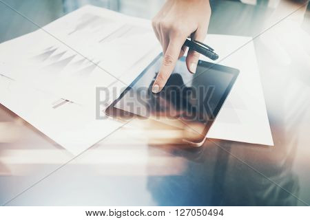 Photo woman working modern tablet and touching black blank screen. Finance investment work process.Banker holding pen for signs documents, markets reports on the table.Horizontal.Film and bokeh