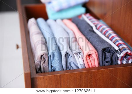 Neatly folded clothes in wooden drawer poster