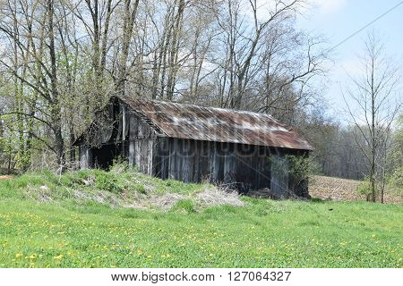 a old barn in disrepair sit on a small hill