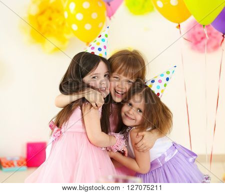 Happy little girls hugging at birthday party