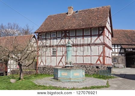 NEU ANSPACH, GERMANY - APRIL 18, 2016: Old half timbered house with fountain at the Hessenpark Open-Air Museum