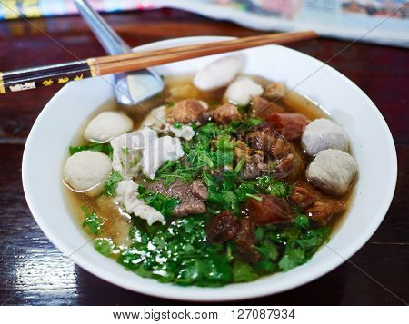 A bowl of soup noodle with fish ball pork and vegetable. Served in a Thai casual restaurant with spoon and chopstick.