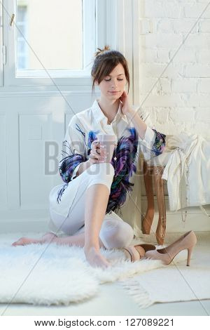 Young woman daydreaming at home, sitting on floor, drinking tea.