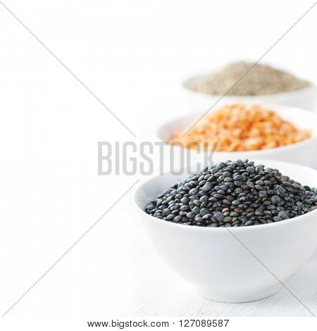 Bowls of assorted dried lentils with red lentils, black beluga lentils and mountain lentils over white