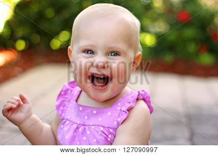 A super happy 10 month old baby girl with new front teeth is smiling as she sits in the garden on a summer day.