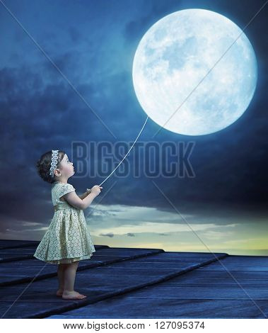 Small girl with moon on a lead