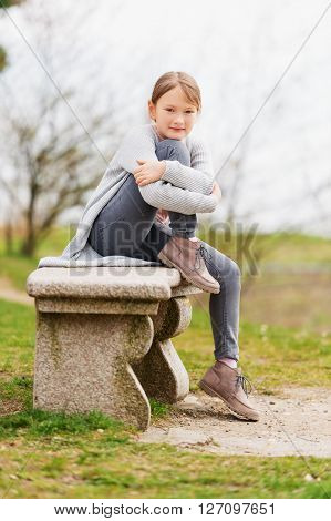 Cute little girl of 8-9 years old sitting on the bench outdoors, wearing grey jeans and cardigan