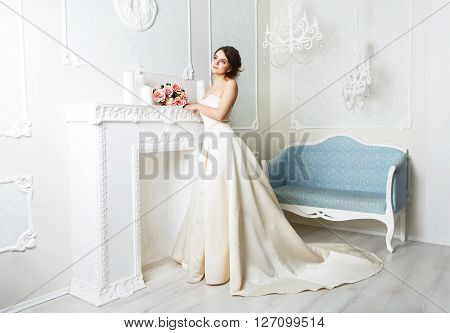 Wedding dress fashion. Beautiful young bride in vintage wedding dress indoors. White wedding dress at model. Girl shows wedding fashion in decorated shabby chic interior with flowers, high key.