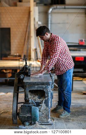 Carpenter working with big electric planer on wooden plank works at the planer joiner's shop workshop