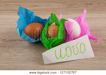 title uovo and beige white bron chicken eggs in paper cover laying on wooden table