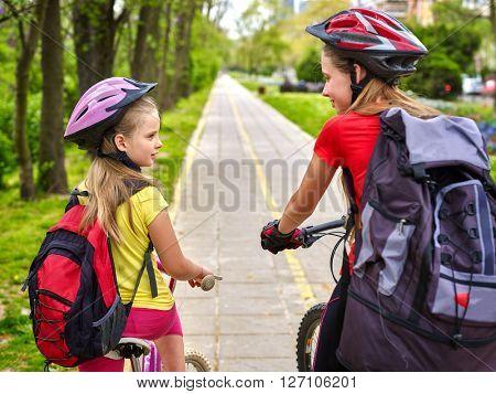 Girls children cycling on yellow bike lane and talk.
