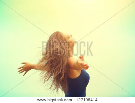 Free Happy Woman Enjoying Nature. Beauty Girl raising hands Outdoor. Freedom concept. Beauty Girl over Sky and Sun. Sunbeams. Enjoyment