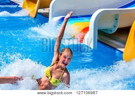 Child on water slide in aquapark.
