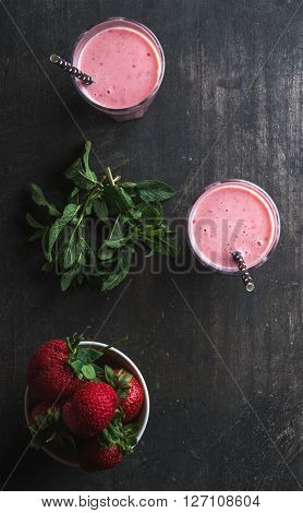 Strawberry and mint smoothie in tall glasses, bawl of fresh berries on dark rustic wood background. Copy space. Top view