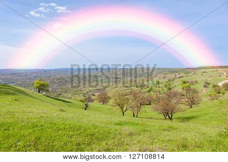 beautiful rainbow appears afte the rain over the green hill