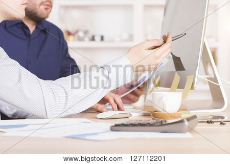 Sideview of businessmen discussing business charts and pointing at computer screen in office