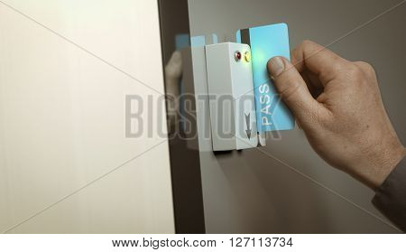 Hand with blue pass card unlocking access to a restricted area. Concept image for security and data protection.