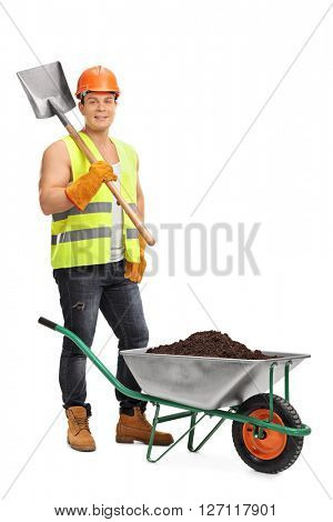 Vertical shot of a young construction worker holding a shovel next to a wheelbarrow full of dirt isolated on white background