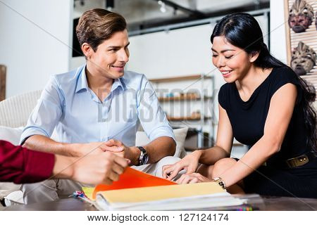 Couple of Caucasian man and Asian woman and shop assistant in furniture store planning furnishing of home together