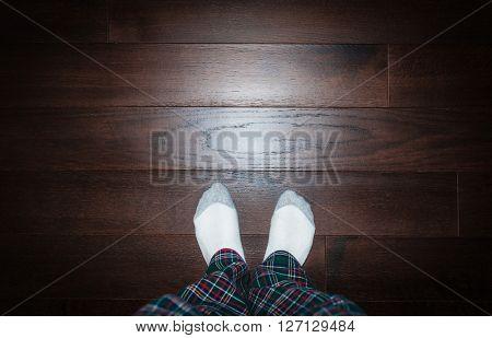 man feet in white sock on oak hard wood floors with copyspace
