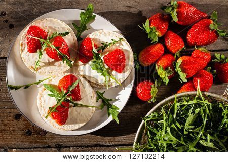 Multigrain rice cakes with strawberries fruit soft mascarpone cheese and arugula for healthy breakfast.