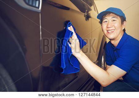 Asian Car Cleaner in blue uniform washing a car with smile (vintage tone)