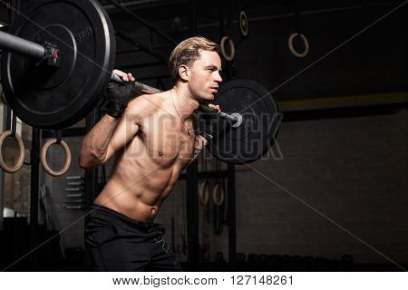 Fit man doing squats with weights on his shoulders
