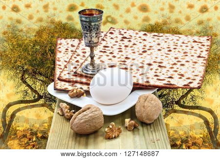 Conceptual collage with olive tree on holy hills of Jerusalem as background and unleavened bread, silver cup of wine and egg and walnuts as foreground for celebration of Jewish Passover