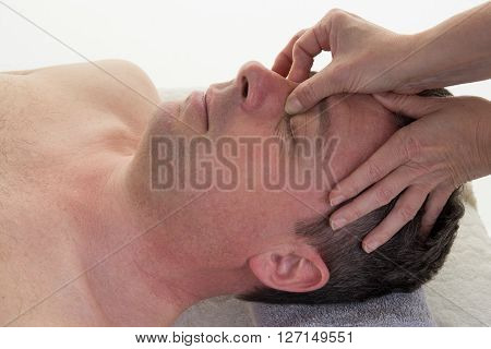 Close Up Head Shot Of Man Having Curative Facial Massage