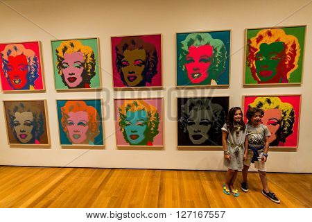 NEW YORK MUSEUM OF MODERN ART - AUGUST 23: A girl stands in the front of the famous Marilyn Monroe picture from Andy Warhole in the Museum of Modern Art in New York an August 23 2015.