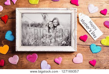 Mothers day composition.  Photo of mother with her daughters in picture frame. Colorful fabric hearts. Studio shot on wooden background.