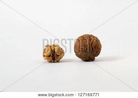 Couple of walnuts in their skins and peeled. Isolate background