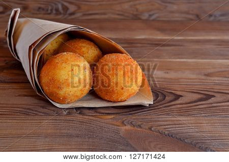 Arancini balls. Fried rice balls in paper on brown wooden background. Snack, sicilian street food