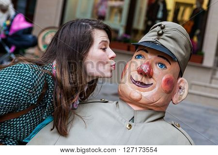 Girl kissing Svejk doll in Czech Rupublic