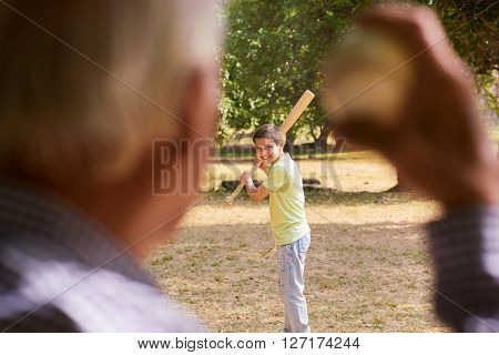 Grandparents spending time with grandson: Senior man playing baseball with his grandson in park. The young kid holds the bat while old man prepares to throw the ball