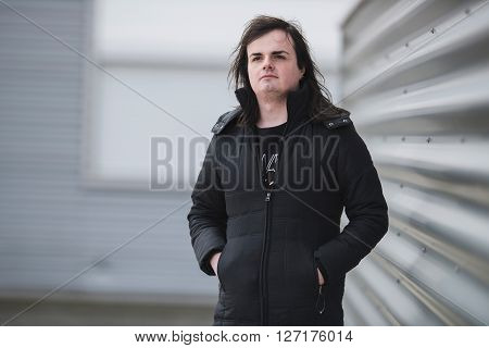Androgenic man wearing black coat in industrial area