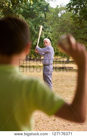 Grandparents spending time with grandson: Senior man playing baseball with his grandson in park. The old man holds the bat while the kid prepares to throw the ball