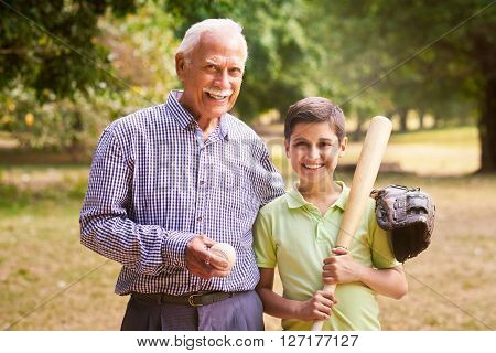 Grandpa spending time with grandson: Portrait of senior man playing baseball with his grandchild in park. The old man embraces the young kid holding the bat smiling and looking at camera
