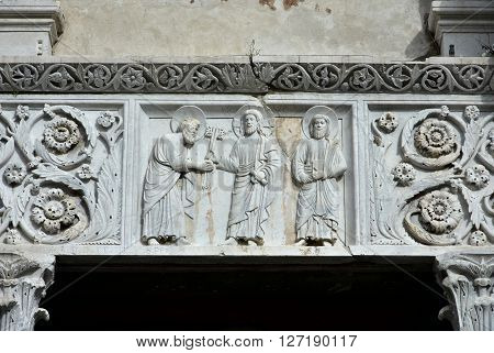 Medieval marble relief from San Pietro Somaldi Church portal with the delivery of the keys made by artist Guido Bigarelli da Como in 1238 in the historical center of Lucca
