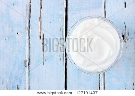 Greek Yogurt In A Bowl, Downward View An A Rustic Soft Blue Wood Background
