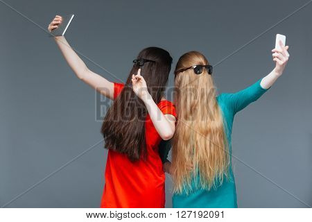 Two funny young women covered face with long hair and taking selfie with tablet and smartphone over grey background