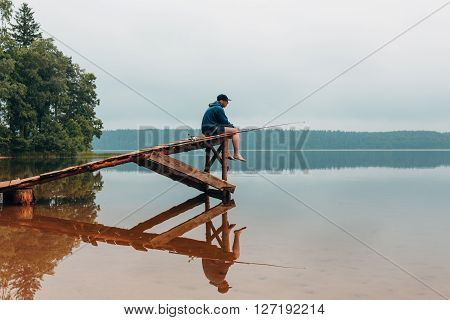 Man sits on a wooden bridge waits when the fish are biting. Weekend photo.