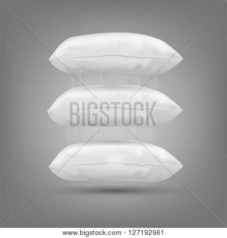Three cushion falling on a gray background