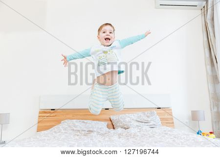 Happy little boy jumping on bed in bedroom