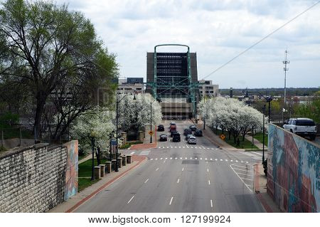 JOLIET, ILLINOIS / UNITED STATES - APRIL 19, 2015: The Jefferson Street Drawbridge, which crosses the Des Plaines River, is raised to allow a boat to pass underneath. Cars wait for the bridge to go down again.