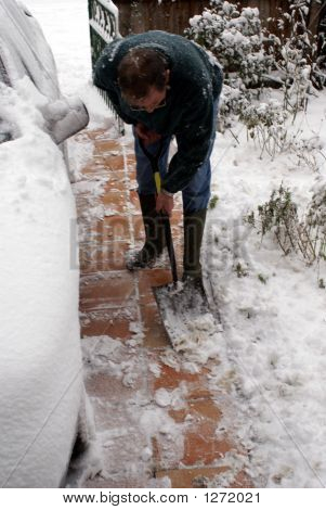 Man Clearing The Snow From The Path.