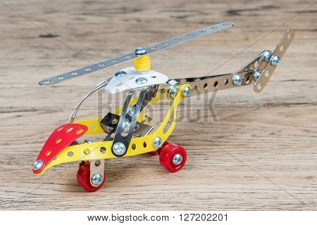 Children helicopter made of iron constructor standing on an old wooden table