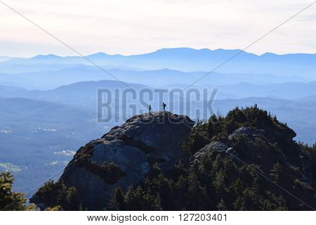 Silhouetted couple standing atop Grandfather mountain, NC. Cascading ridges of blue mountains on the horizon